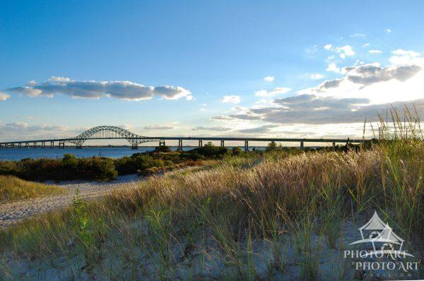 The image is showing several grassy dune hills in the foreground. Captree bridge in the background,