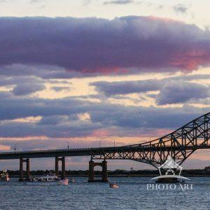 Robert Moses Bridge with a summer's purple and pink sunset in the background.