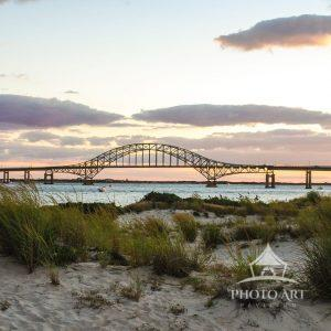 The soft hue of purple, pinks, and slight orange sunset behind the Robert Mosses bridge.