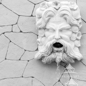 A black and white image captures the details of a white stone wall fountain.