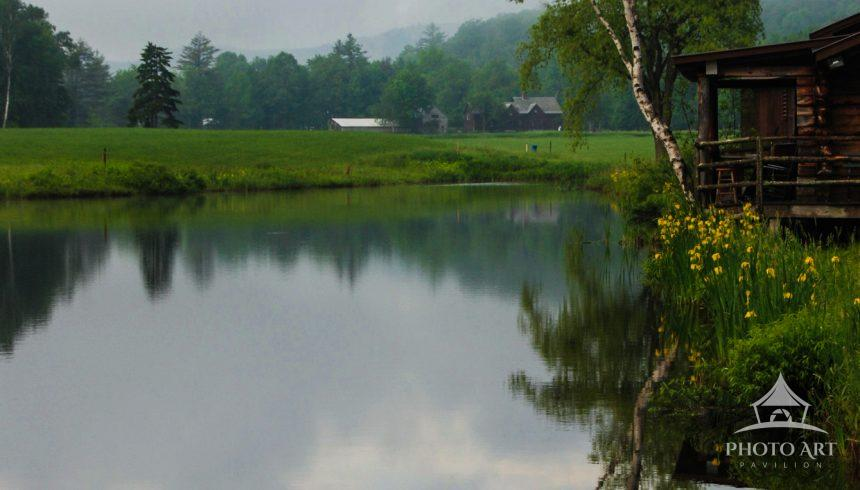 Image of a still pond in the early morning. A wood cabin is at the edge of the lake, which is