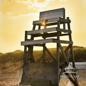 A beautiful sunset comes shining through an empty life guard chair at the end of a warm summer day