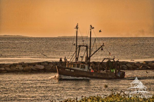 Montauk Point fishing boat heads into harbor between the jetties as the sun begins to set.