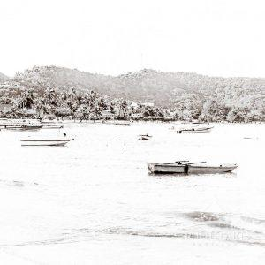 Tiny boats dot the cove of Grand Anse Beach in Grenada. This seascape has been digitally processed