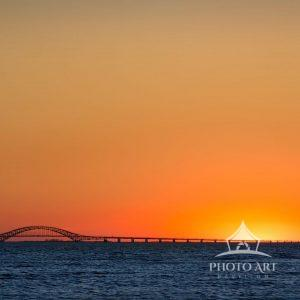 A lone seagull makes its way back to its nest as the sun sets over the Great South Bay with Fire