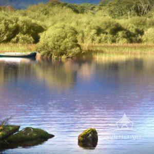 A lone boat waits along an island shoreline of a tranquil lake near the Ross Castle in Killarney,