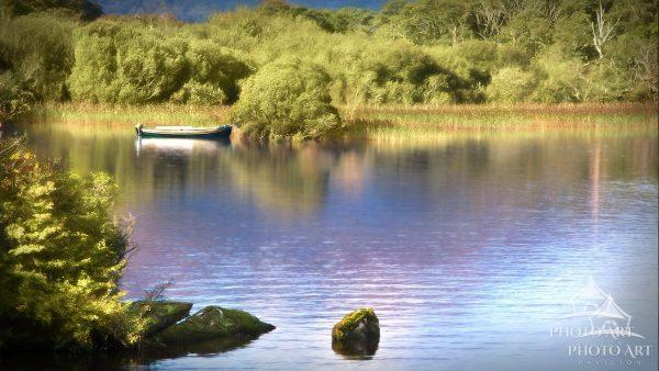 A lone boat waits along an island shoreline of a tranquil lake near the Ross Castle in Killarney,