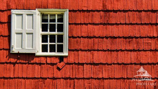 An Architectural Detail of a bright red colonial home located in the Old Bethpage Village