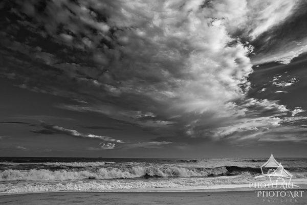 Exiting storm clouds journey into the unknown as the ocean waves crash upon the shore. If you look