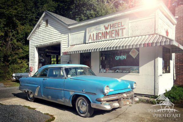Old service station and vintage car along the side of a rural, countryside road. Color photograph.