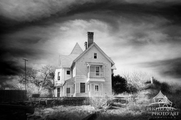 Almost like a scene from a horror movie, an old house up on a hill under an unusual, swirly sky and