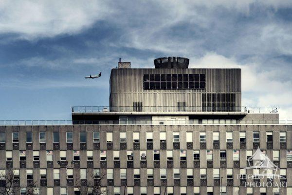 A building in Queens, NY with lots of American Flags in the windows and a plane ready to land at JFK