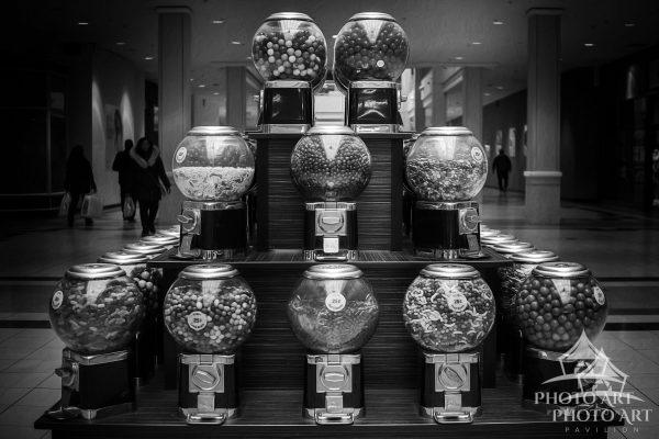 Old gum ball machines in the mall in Nassau County, NY. Black and white photograph with subtle