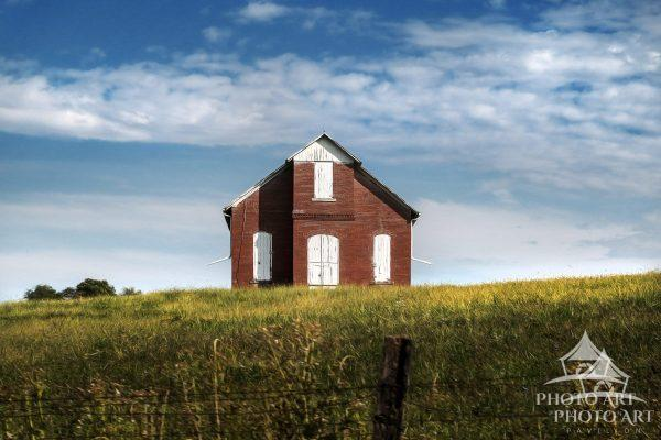 Farm life and an single building in the middle of a field, on a hill. Americana scene from the
