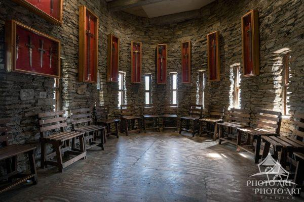 Knights' room in an amazing old castle in America. Seats with swords above them, for members