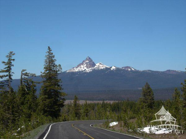 On the road with Mt. Hood in the distance. This was taken while riding on the back of a motorcycle
