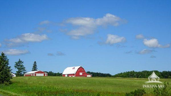 A red barn in a green meadow under a big blue sky.