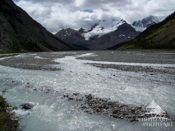 Rocky riverbed with flowing water surrounded by mountains with a glacier.