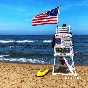 The lifeguard patrols the ocean while the American Flag waves in the wind at the beach in Ocean