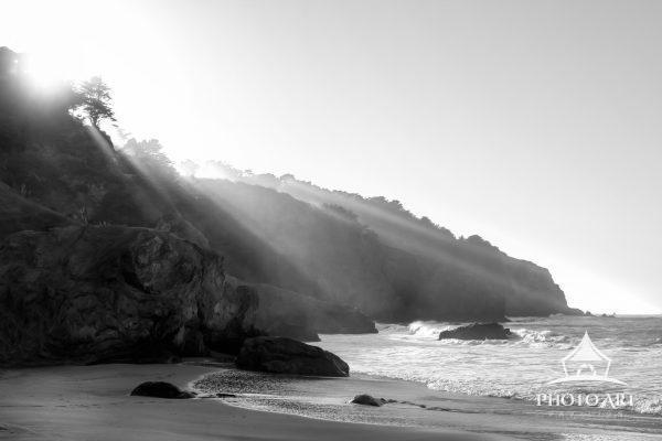 Sun rays come over the tops of the cliffs along the Pacific Ocean near San Francisco, California.