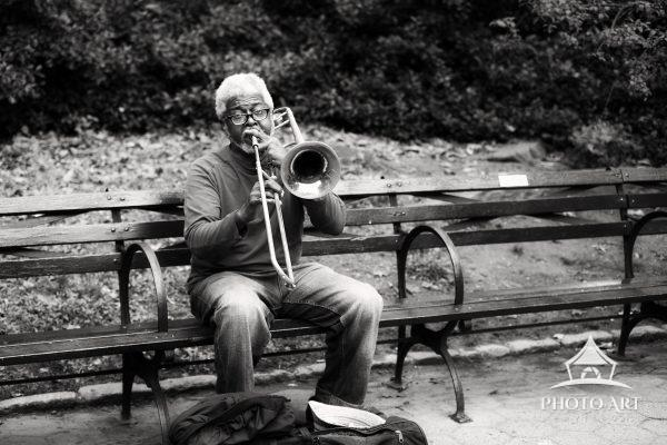 A New York City trombone player in Central Park on an autumn day. Black and white photograph.