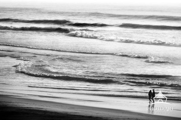 Couple walking along the shore of the Pacific Ocean on a misty day near San Francisco, California.