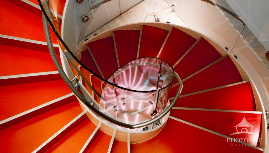 Looking down red spiral staircase.