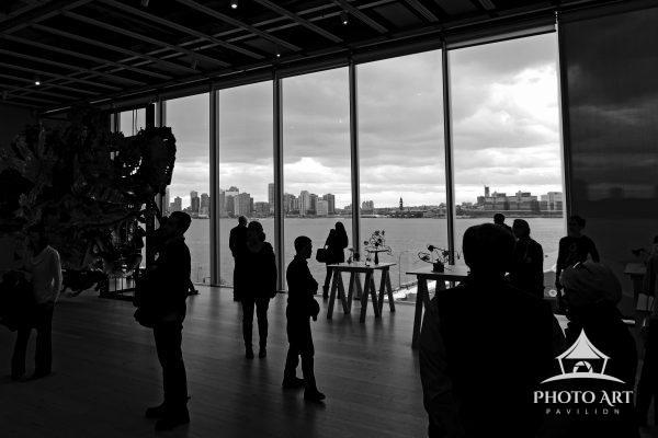 Visitors at the Whitney Museum in NYC are looking out over the Hudson River to New Jersey while they