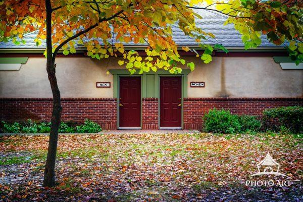 Closed restroom in a park on Long Island. Autumn color and fall foliage highlight the starkness of