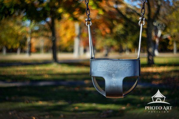 Single child's swing quiet and alone in an empty park as the weather begins to get cold. Autumn