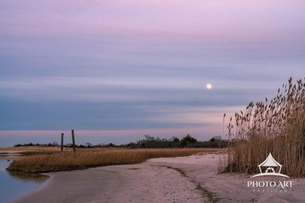 Moon rising right after sunset on the beach.