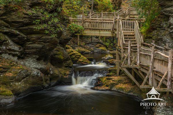 Rustic Boardwalk trail along the Bushkill Falls Trail. The trail crosses and follows river as it