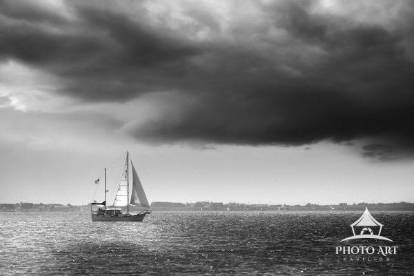 Unique and classic sailboat, sailing along The Great South Bay under dramatic clouds. Typical summer