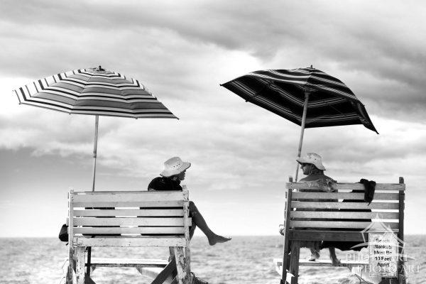 Two lifeguards sit and chat on their lifeguard chairs, protected from the sun under their large