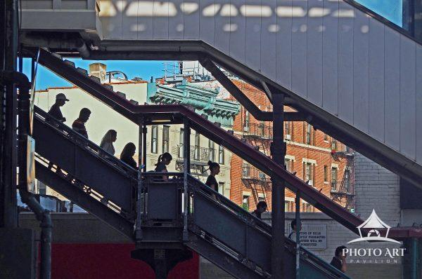 Commuters descend stairs from elevated train