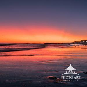 The sunset puts on a gorgeous afterglow illuminating the sand and surf.