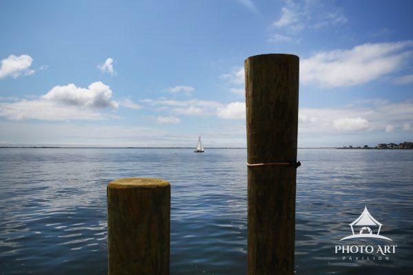 Tiny white sailboat in Great South Bay passing by