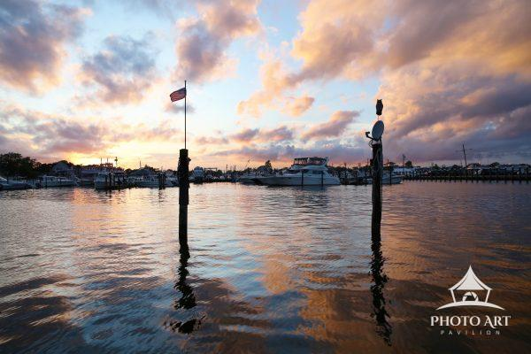 Sunset glistening over the Bay Shore Marina, Long Island. American flag and owl statue become