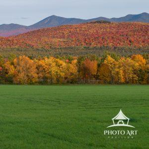 Autumn colors of the Whiteface Mountain Range from the West with green field foreground.