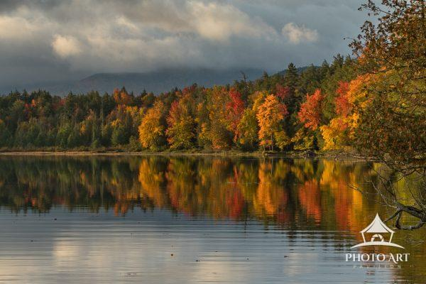 Fall colors reflected in the calm early morning waters of the Saranac Boat Launch.