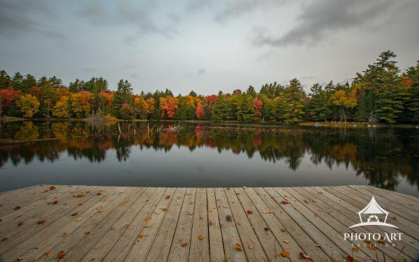 Fall colors reflected beyond the dock of Church Pond, Adirondacks NY