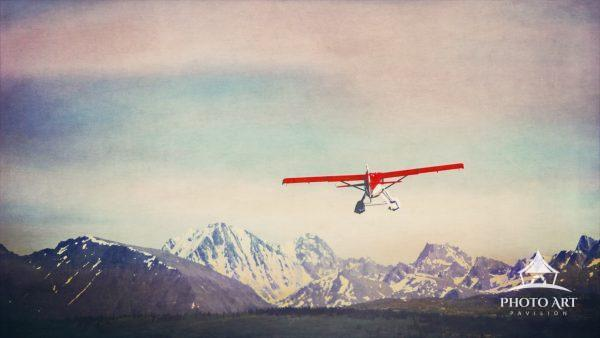 A little red float plane takes off from the water, heading toward the mountains of the Alaska Range.
