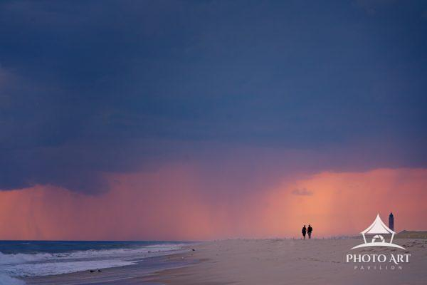 Beautiful sunset on the beach with rain and stormy clouds on the horizon.