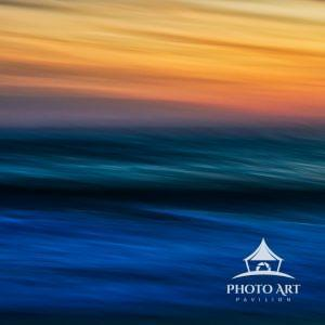 Colorful capture of the sun setting over the ocean using intentional camera movement