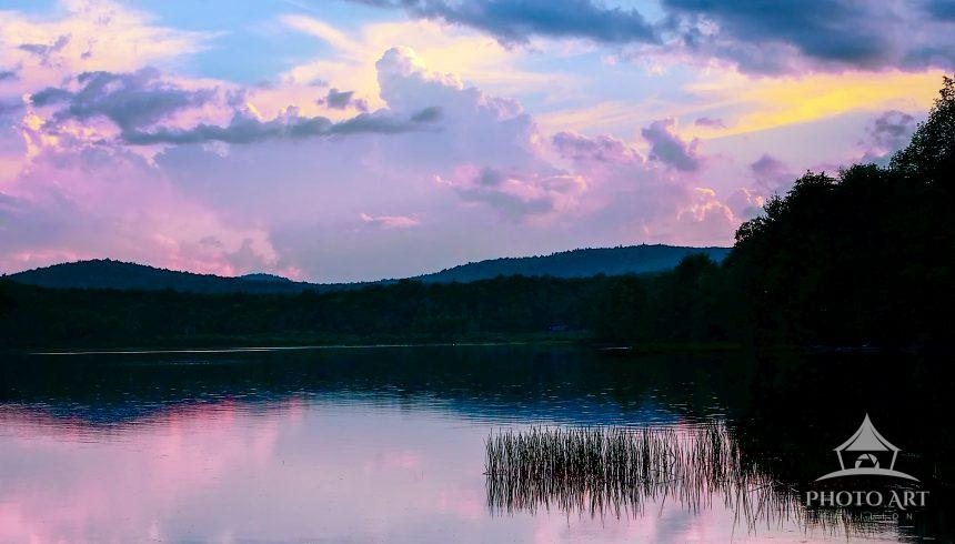 A tranquil magenta glows bathes an Adirondack lake after sunset creating a tranquil scene.