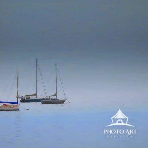 This group of sailboats enshrouded in dense fog appears to be floating in space while anchored in