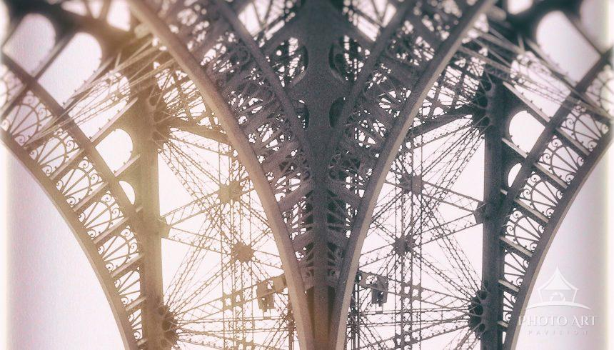 A view of the iron lattice work of the Eiffel Tower shot on film with a manual film camera