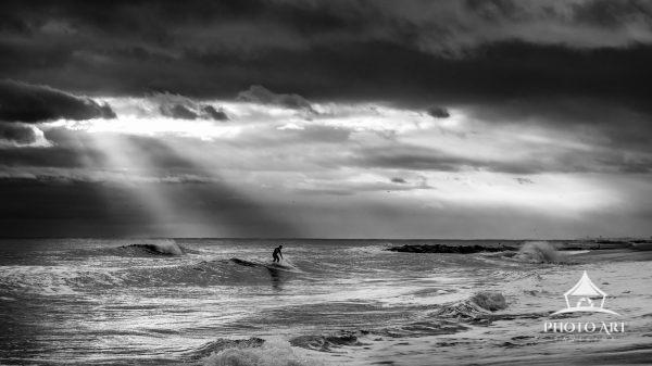 A surfer riding in of rays of light at Long Beach, Long Island.