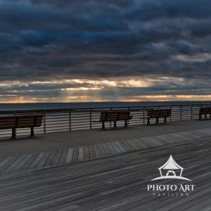 The boardwalk is void of people, the clouds in the sky create sun rays as the sun begins to set.