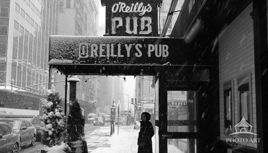 Snow coming down outside of O'Reilly's Pub in Midtown Manhattan, NYC
